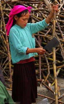 A young girl cutting bamboo for a sale